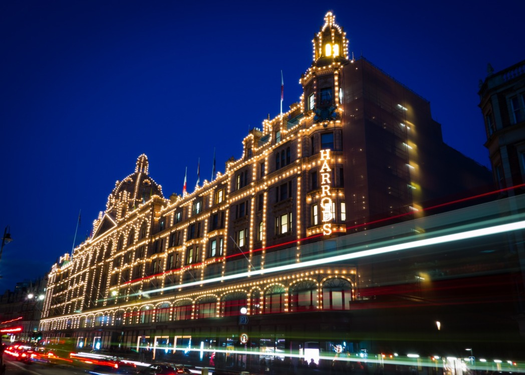 Harrods by night verlicht met een rode Londense bus
