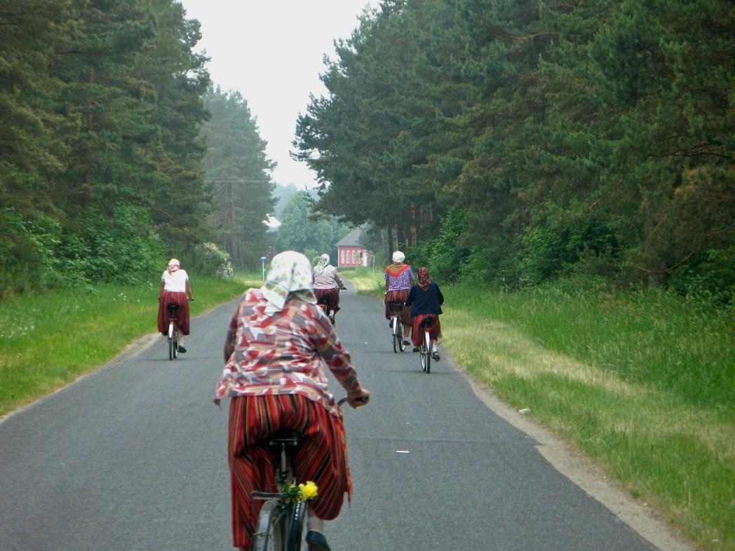 Fietsende vrouwen in klederdracht op het eiland Kihnu in Estland